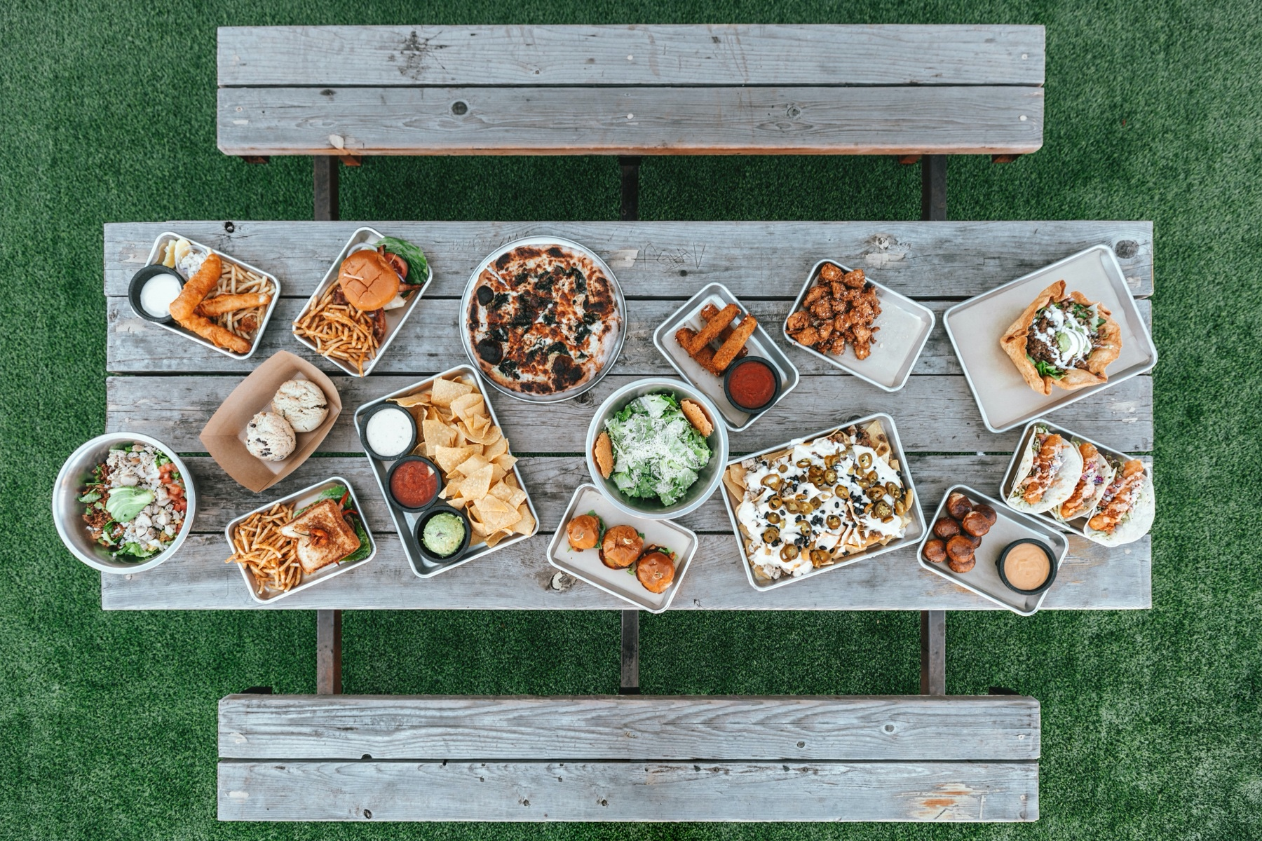 Aerial view of picnic table with various food items displayed on it.