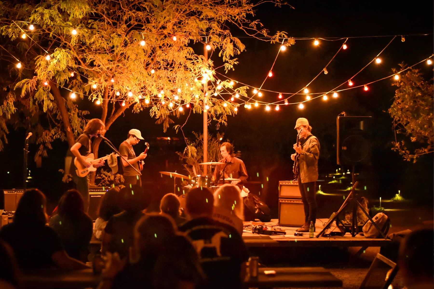 Photo of a rock band playing outside at night.