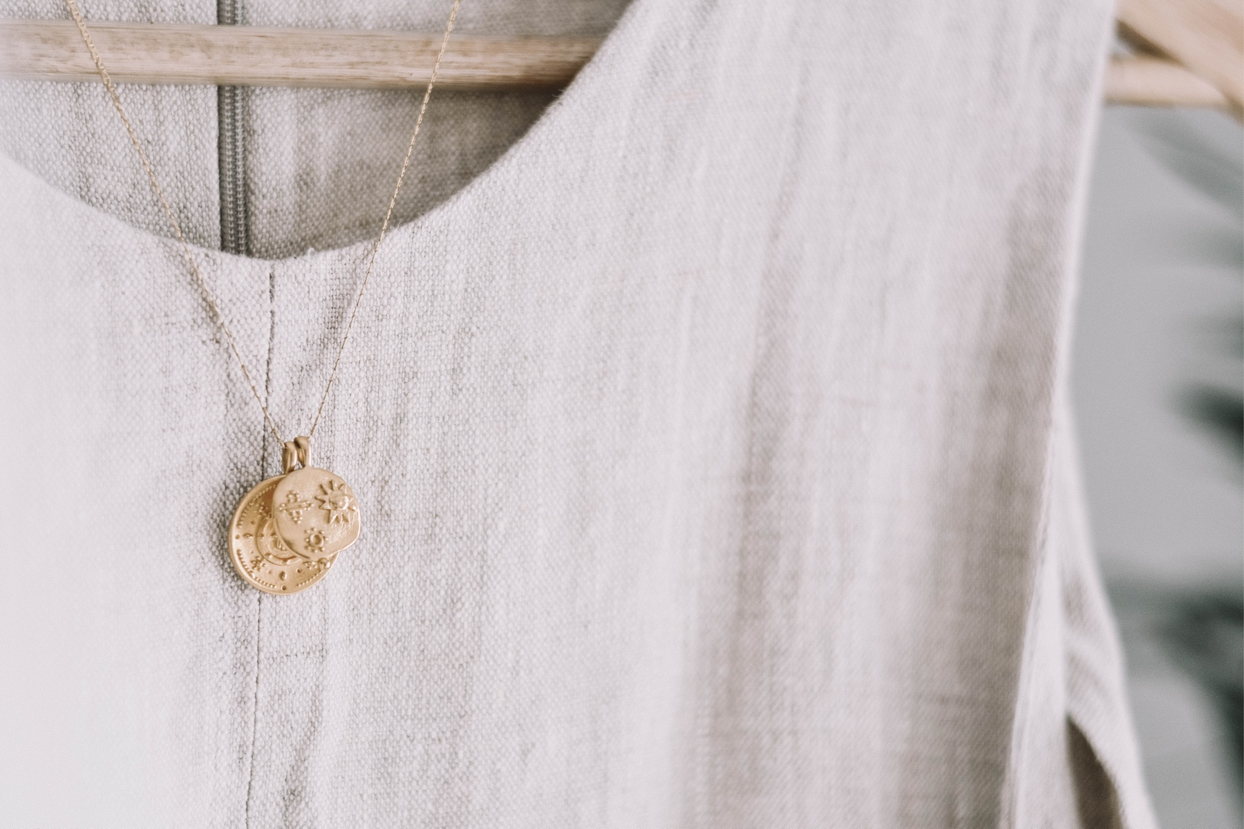 Photo of a gold necklace on a hanger with a linen shirt.