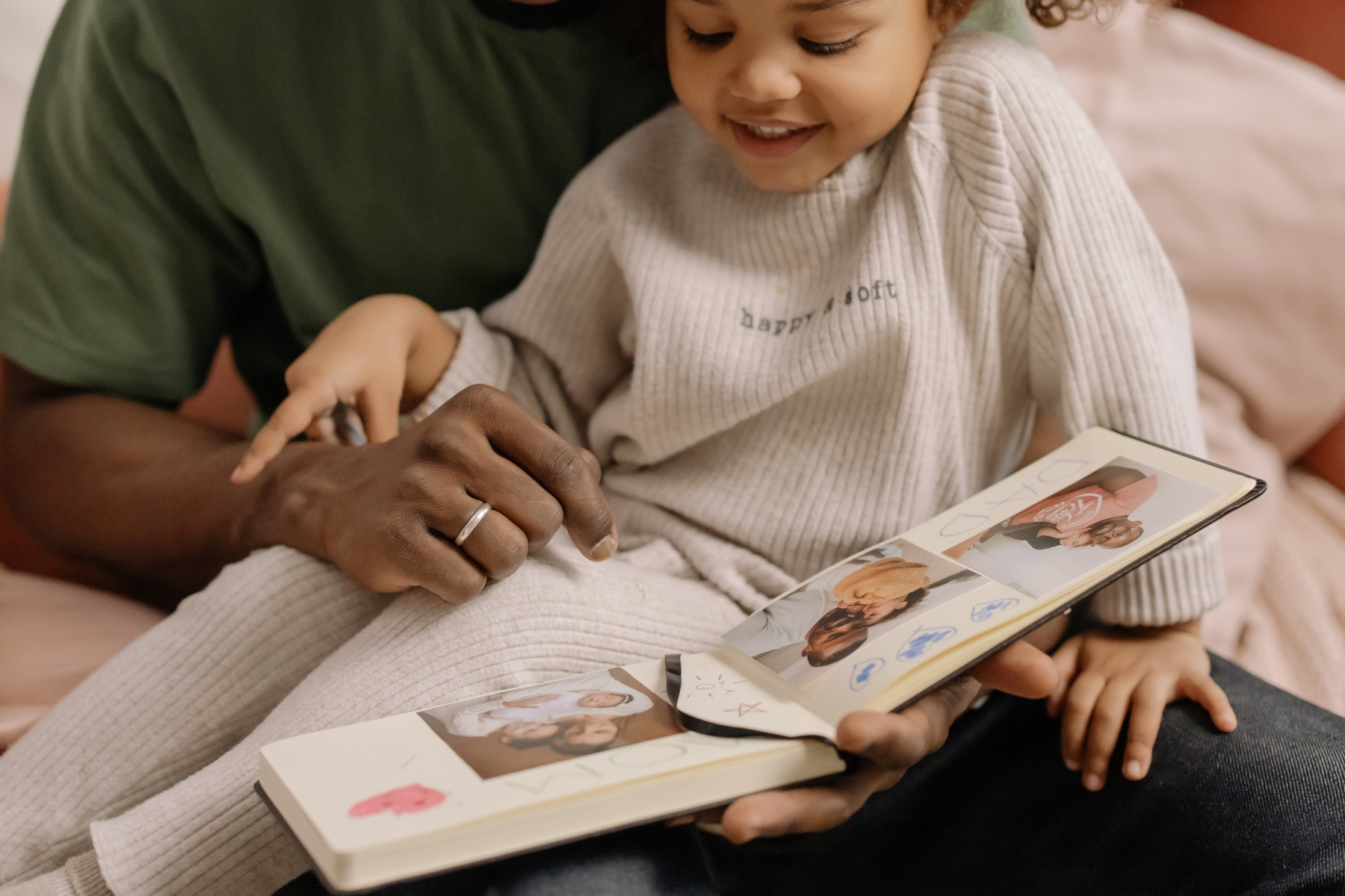 A father and young daughter look through a photo album together.
