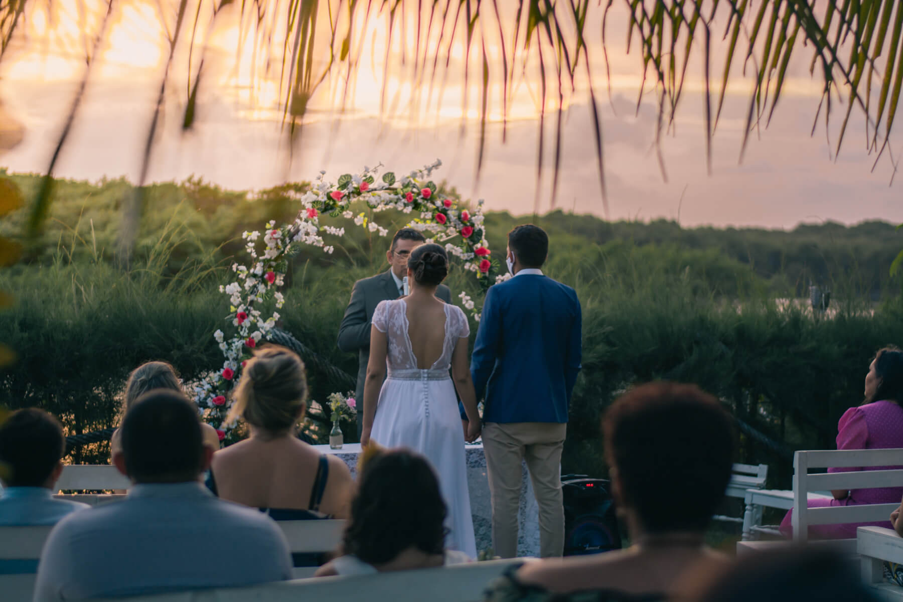 A couple with their officiant under a floral arch.