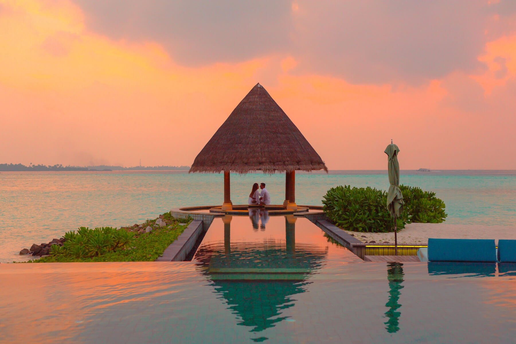 A couple under a tropical pagoda at sunset in front of a reflecting pool