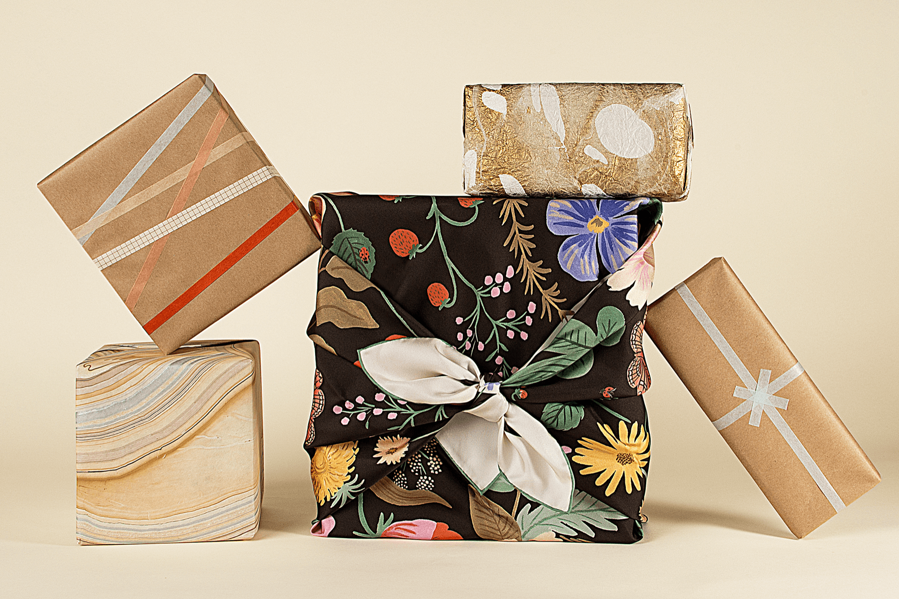 Stack of eco-friendly wrapped gifts on a beige background.