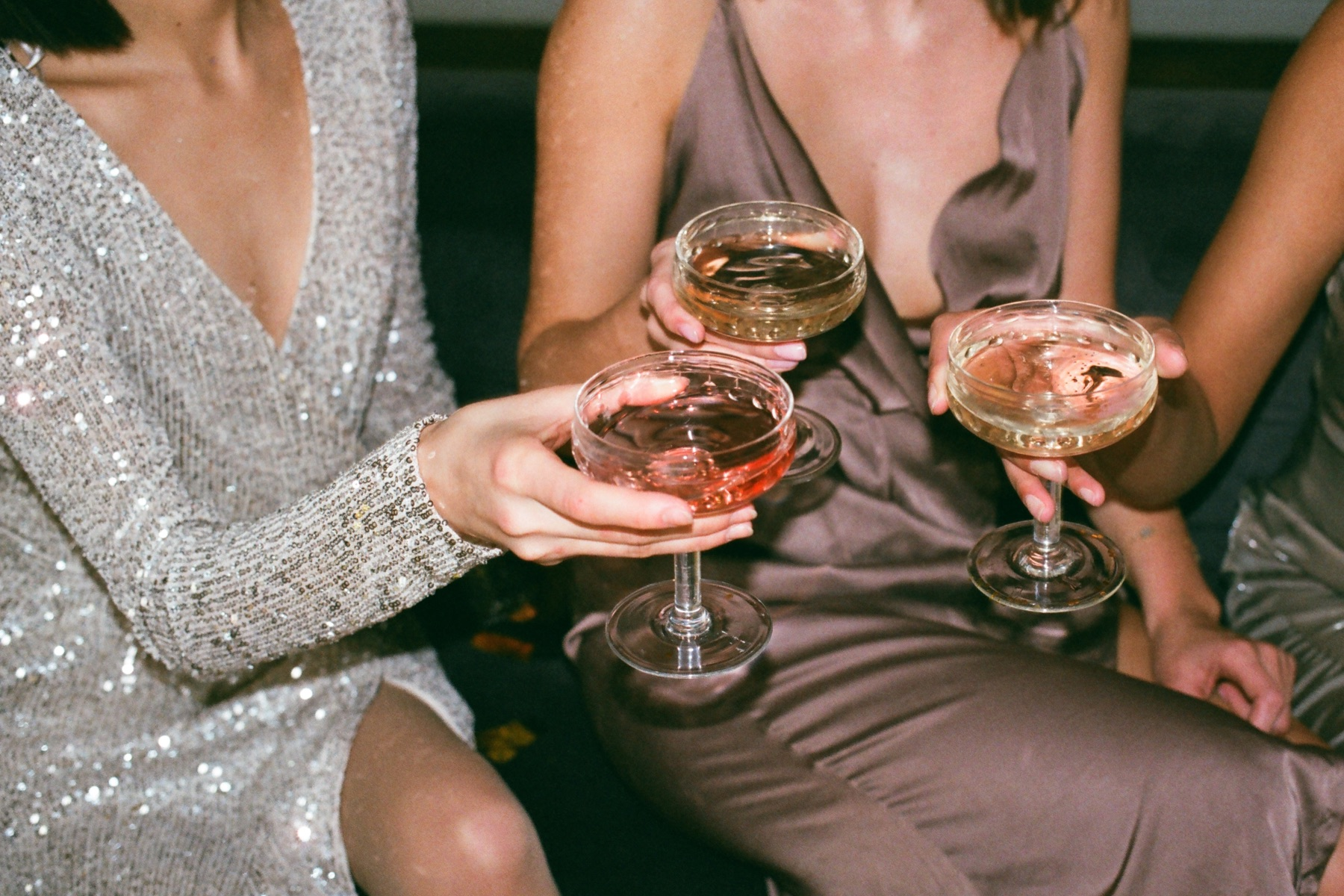 Image of three women toasting their cocktails while wearing fancy evening attire.