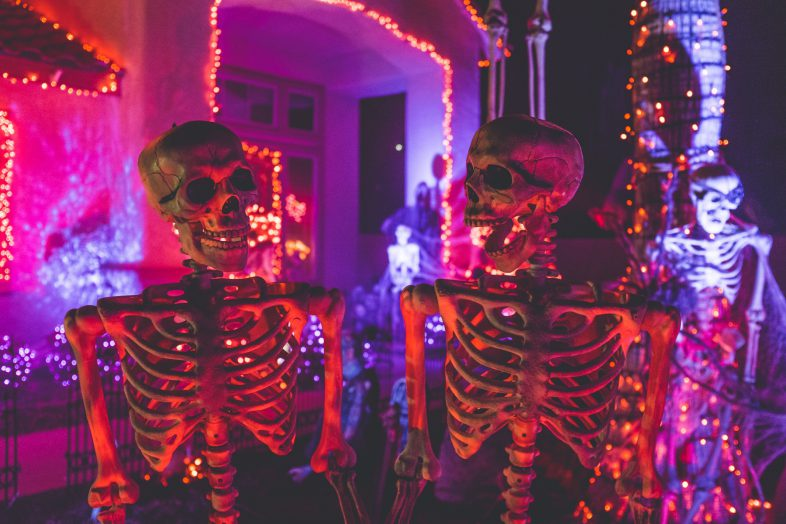 Photo of two skeleton decorations standing in front of a doorway at night backlit in pink and purple lights.