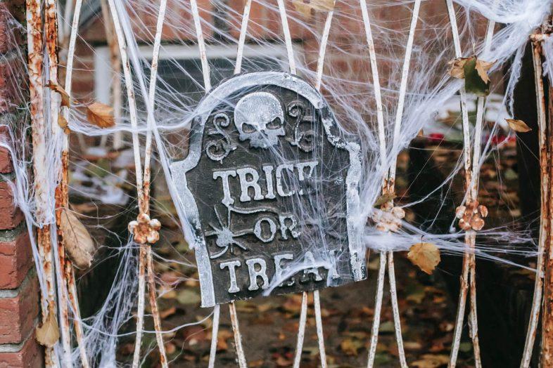 Photo of Halloween decor—a gravestone and cobwebs.