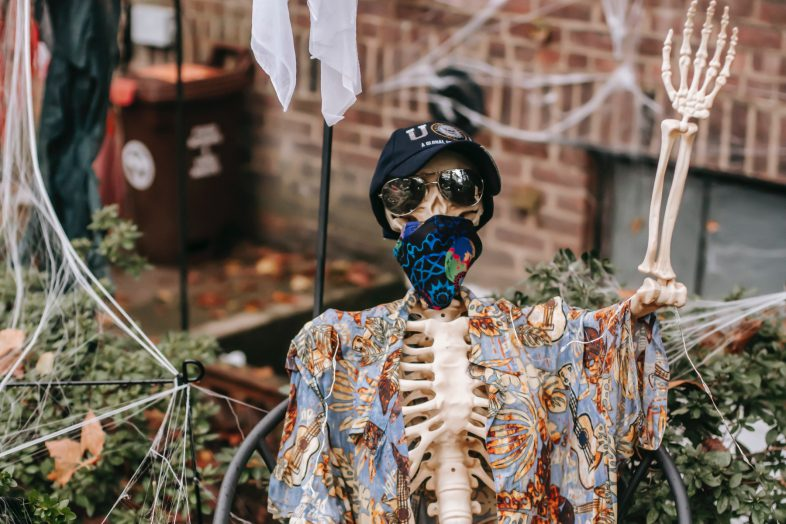 Photo of a skeleton decoration wearing clothing and waving its hand in a yard.