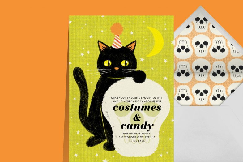 """""""Black Cat"""" invitation by Paperless Post. The green card features a black cat in a party hat placing its paw on a large skull. The card appears on an orange background."""