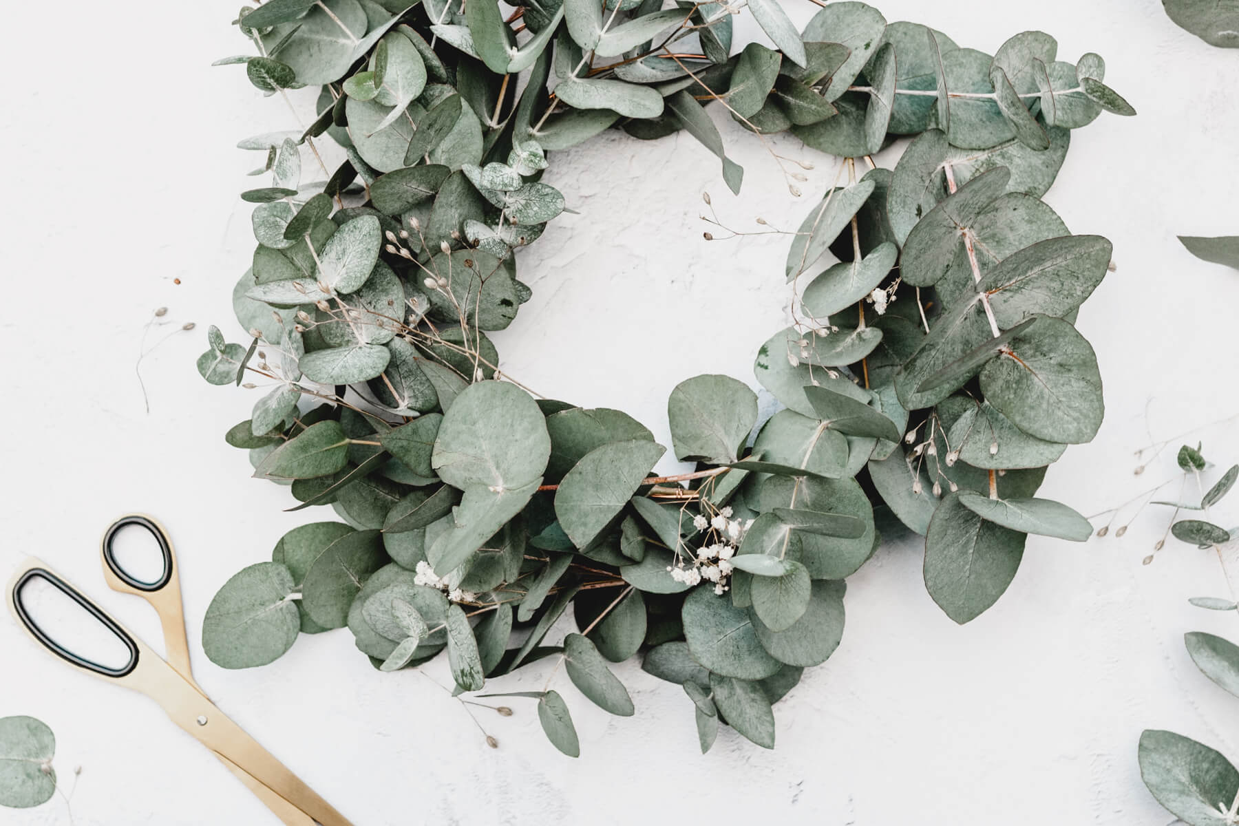 outdoor wreath-making parties are a great way to host covid Christmas safely featuring an image of a eucalyptus wreath