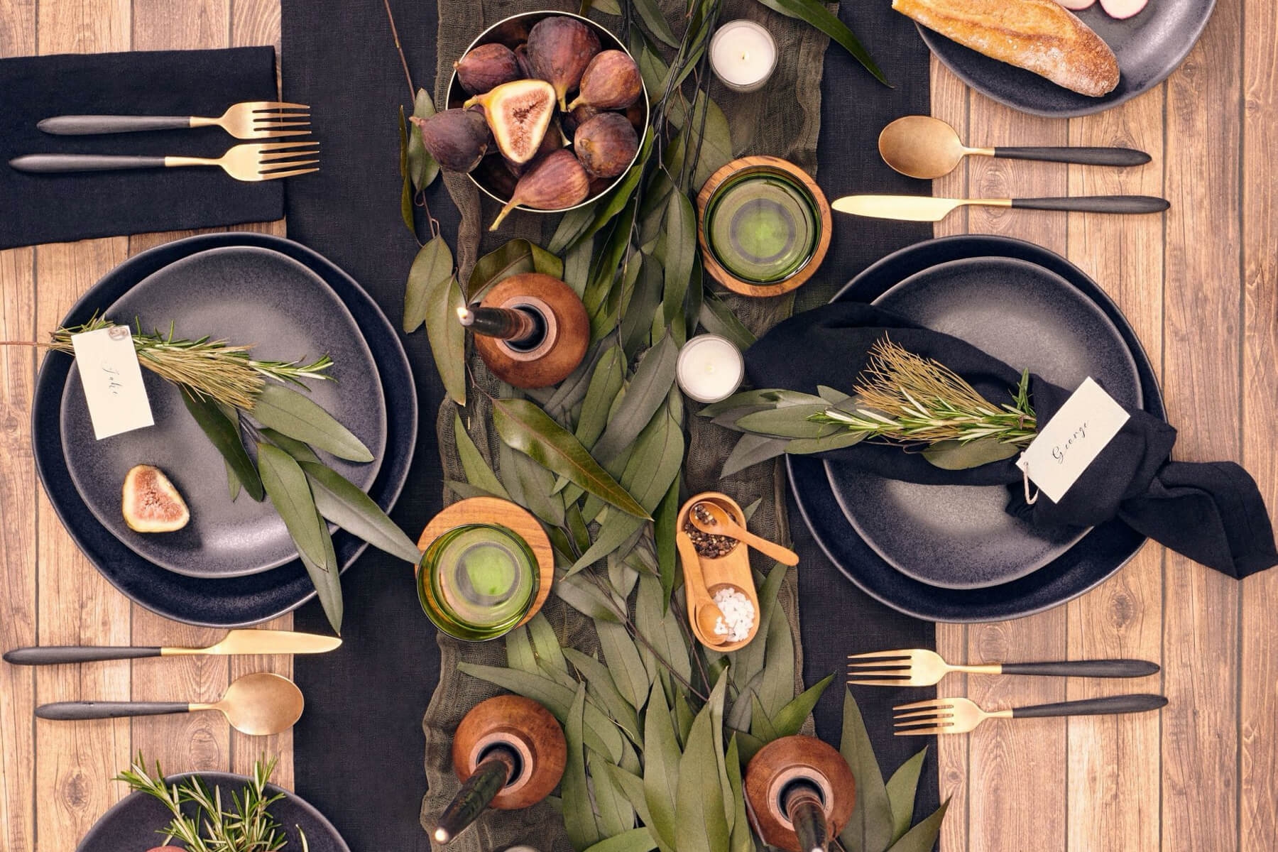 Dark Nordic table from Social Studies with dark plates and a eucalyptus table runner