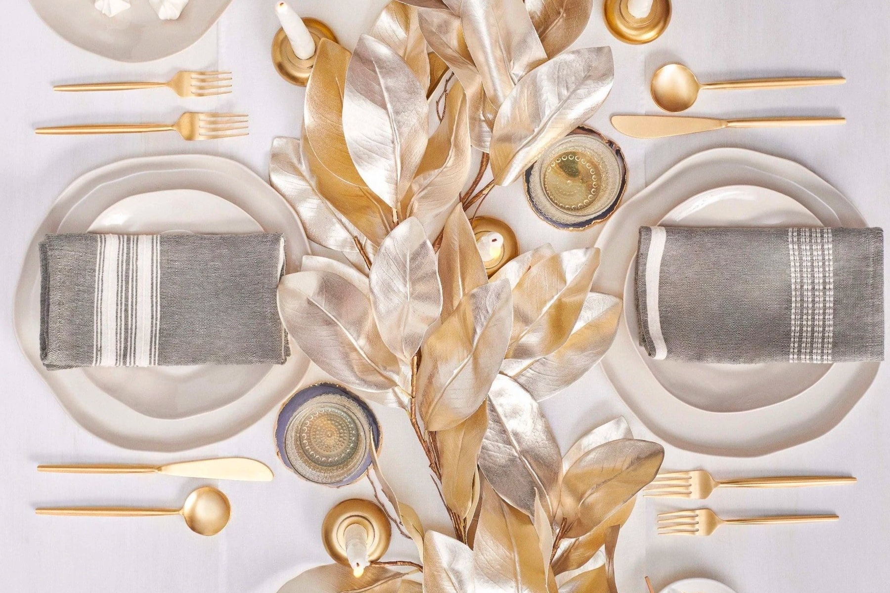 white and gold tablesetting from Social Studies featuring gold and silver leaves