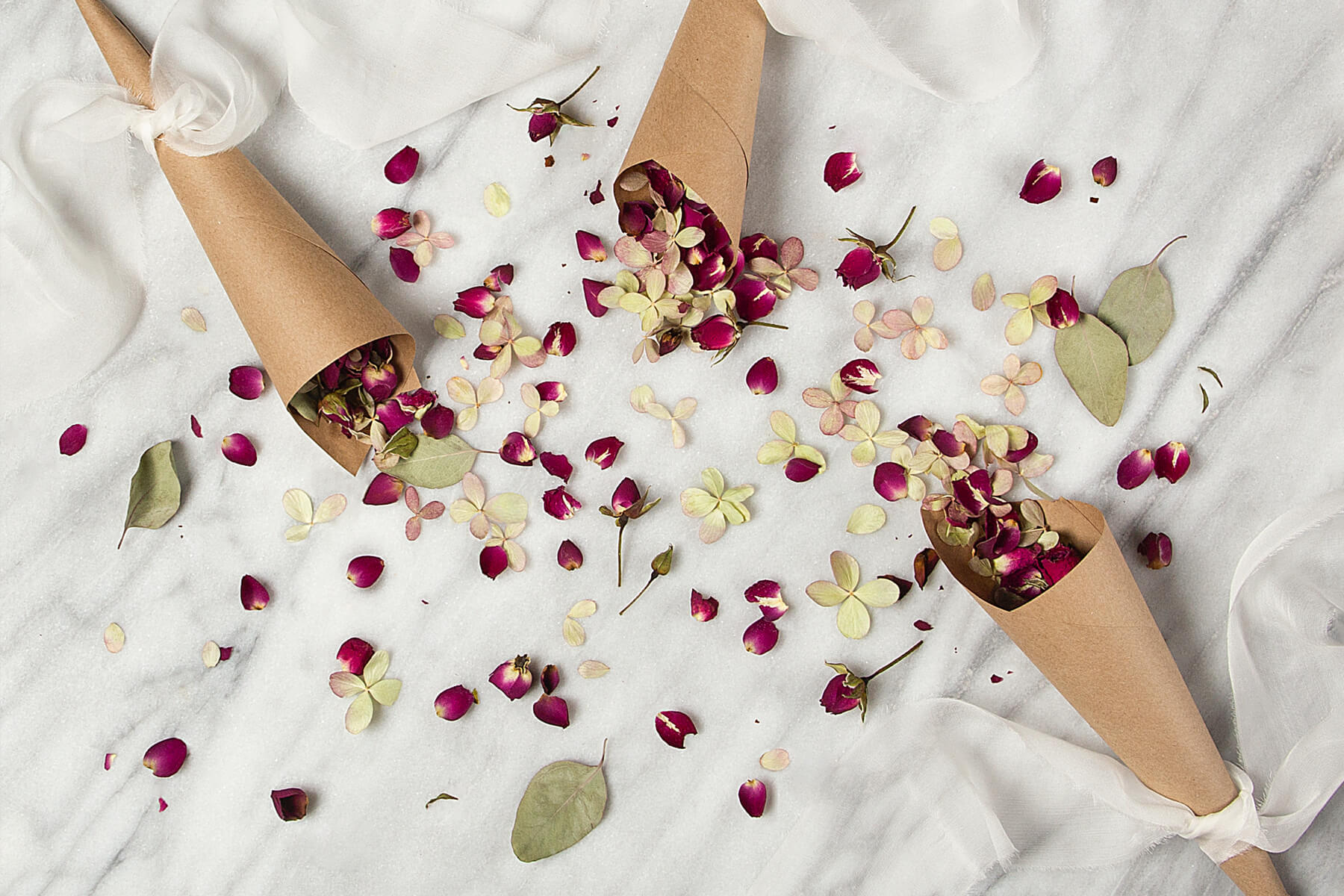 Floral confetti spread out on a white tablecloth.