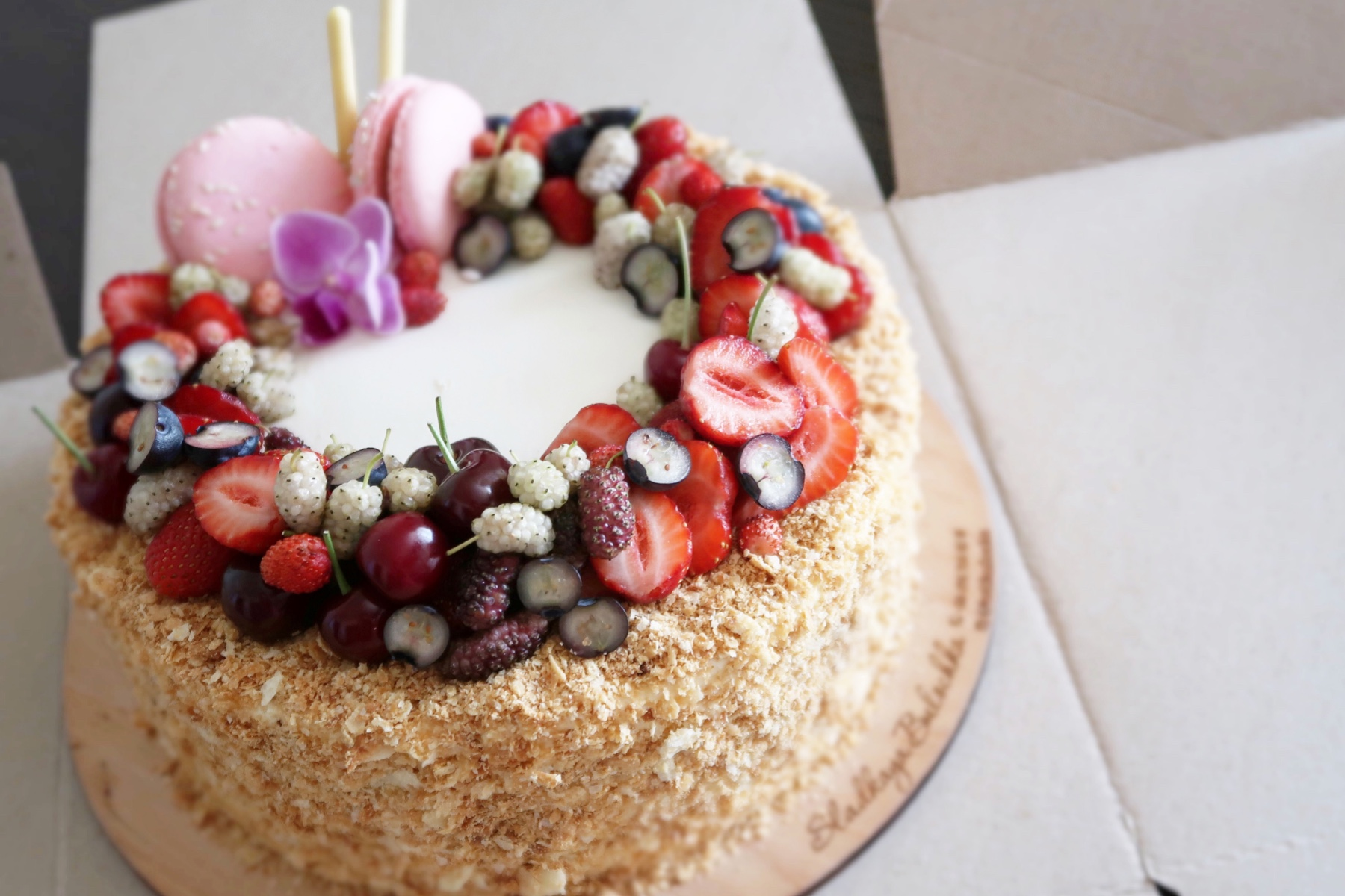 Photo of a cake covered in strawberries, macarons, and other treats