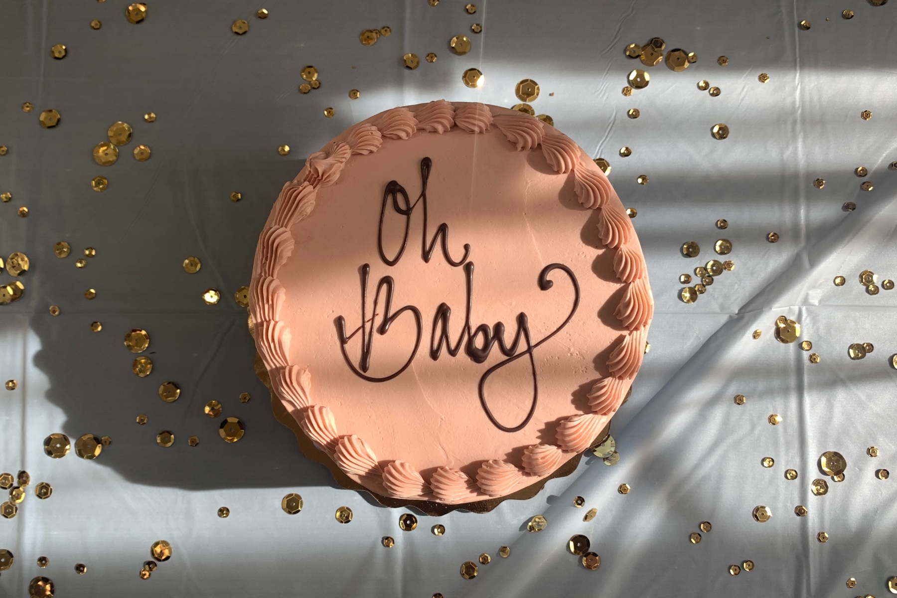 """Photo of a cake with the phrase """"Oh Baby"""" in script"""