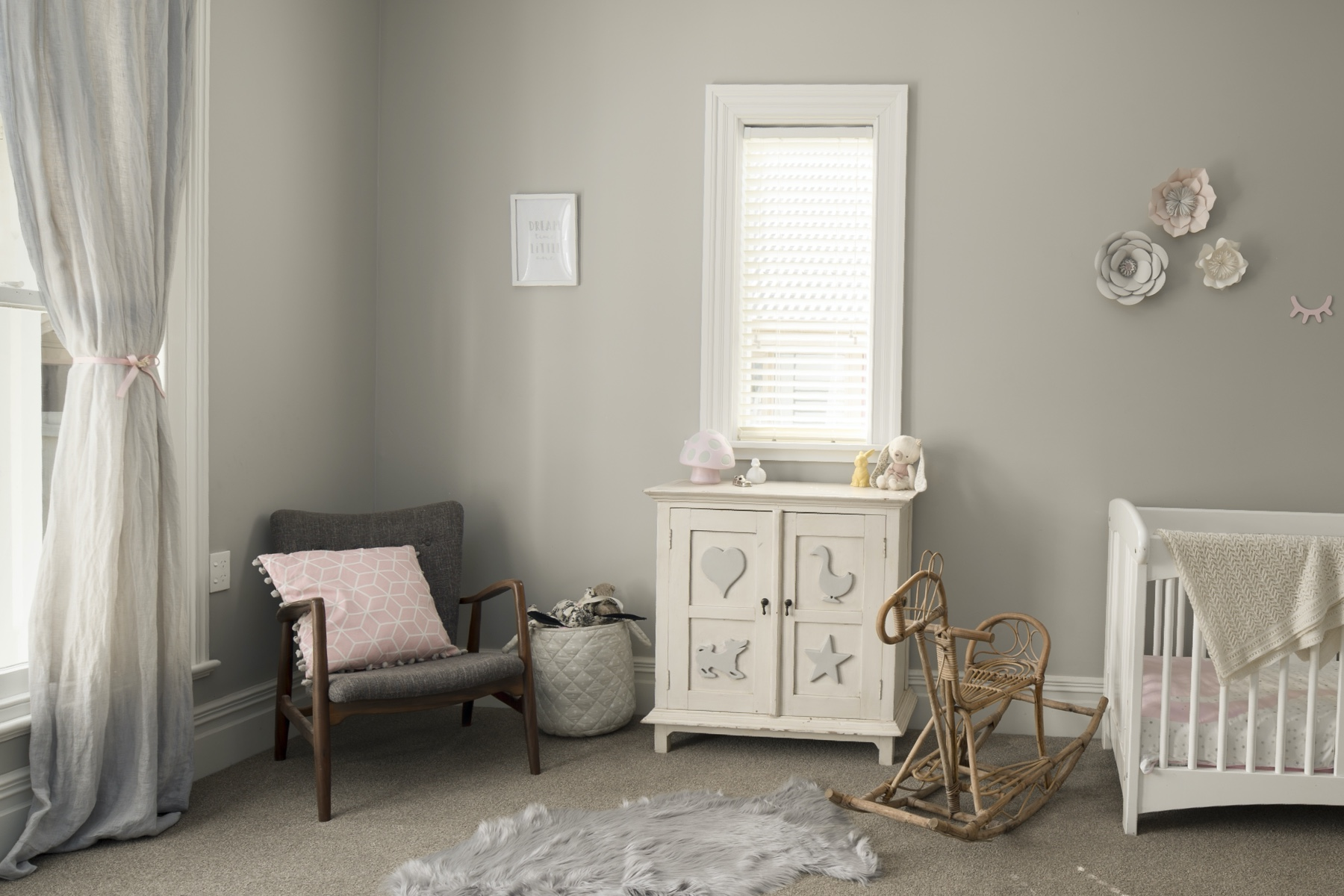 Photo of a nursery featuring a chair, changing table, and rocking horse.